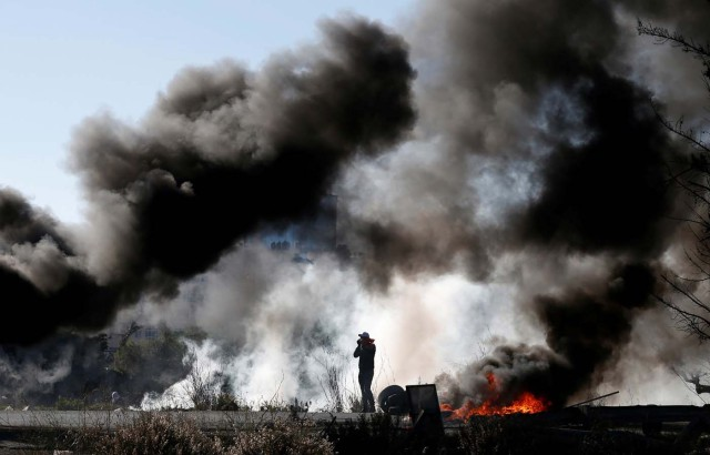 "A Palestinian protester is seen as smoke rises from burning tires during clashes with Israeli troops as Palestinians call for a ""day of rage"" in response to U.S. President Donald Trump's recognition of Jerusalem as Israel's capital, near the Jewish settlement of Beit El, near the West Bank city of Ramallah December 8, 2017. REUTERS/Mohamad Torokman"