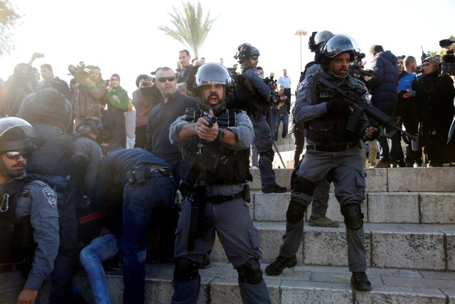"An Israeli policeman aims his weapon as his comrades detain a Palestinian during scuffles at Damascus Gate after Friday prayers in Jerusalem's Old City, as Palestinians call for a ""day of rage"" in response to U.S. President Donald Trump's recognition of Jerusalem as Israel's capital December 8, 2017. REUTERS/Baz Ratner"