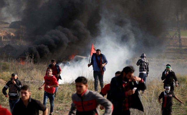 "Palestinian protesters run for cover during clashes with Israeli troops as Palestinians call for a ""day of rage"" in response to U.S. President Donald Trump's recognition of Jerusalem as Israel's capital, near the border with Israel in the east of Gaza City December 8, 2017. REUTERS/Mohammed Salem"