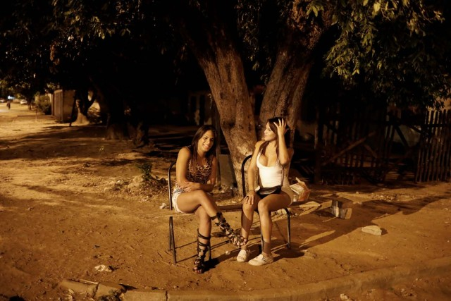 "Transsexuals Camila (R), 23, and Valeria, who left Venezuela nine months ago and are sex workers, wait for customers on a street in Boa Vista, Roraima state, Brazil November 18, 2017. Camila said she turns tricks and earns about $100 a night - enough to send food, medicine and even car parts to her family in Ciudad Bolivar. ""Things are so bad in Venezuela I could barely feed myself,"" said Camila, who declined to give her last name. REUTERS/Nacho Doce SEARCH ""VENEZUELAN MIGRANTS"" FOR THIS STORY. SEARCH ""WIDER IMAGE"" FOR ALL STORIES."