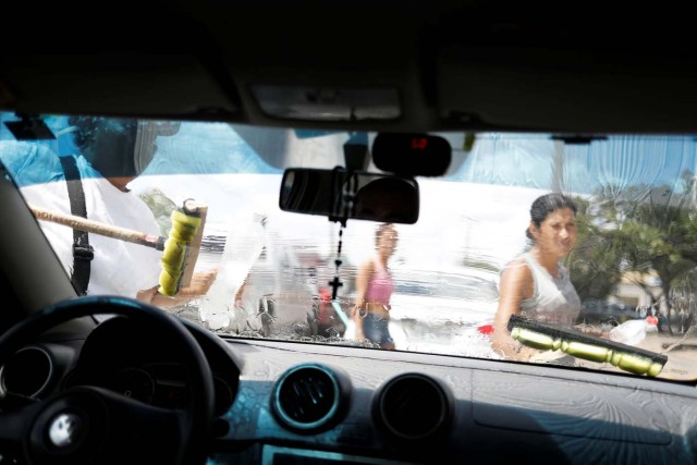 "Venezuelans wash car windows at traffic lights in Boa Vista, Roraima state, Brazil November 17, 2017. REUTERS/Nacho Doce SEARCH ""VENEZUELAN MIGRANTS"" FOR THIS STORY. SEARCH ""WIDER IMAGE"" FOR ALL STORIES."