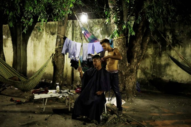 "A Venezuelan man cuts hair of his friend at a gym which has turned into a shelter for Venezuelans and is run by Civil Defense with meals provided by Evangelical churches in Caimbe neighbourhood in Boa Vista, Roraima state, Brazil November 17, 2017. REUTERS/Nacho Doce SEARCH ""VENEZUELAN MIGRANTS"" FOR THIS STORY. SEARCH ""WIDER IMAGE"" FOR ALL STORIES."