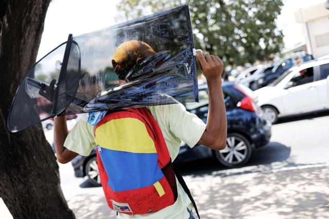 "A Venezuelan man wears a backpack with the colours of Venezuelan flag as he sells car accessories at traffic lights in Boa Vista, Roraima state, Brazil November 18, 2017. REUTERS/Nacho Doce SEARCH ""VENEZUELAN MIGRANTS"" FOR THIS STORY. SEARCH ""WIDER IMAGE"" FOR ALL STORIES."