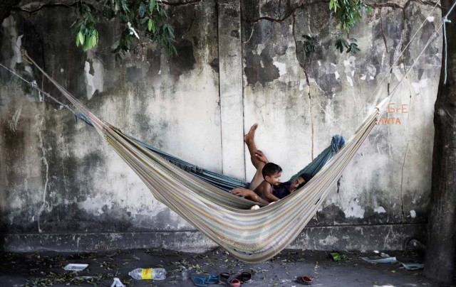 "A family rests in a hammock outside a gym which has turned into a shelter for Venezuelans and is run by Civil Defense with meals provided by Evangelical churches in Caimbe neighbourhood in Boa Vista, Roraima state, Brazil November 17, 2017. REUTERS/Nacho Doce SEARCH ""VENEZUELAN MIGRANTS"" FOR THIS STORY. SEARCH ""WIDER IMAGE"" FOR ALL STORIES."