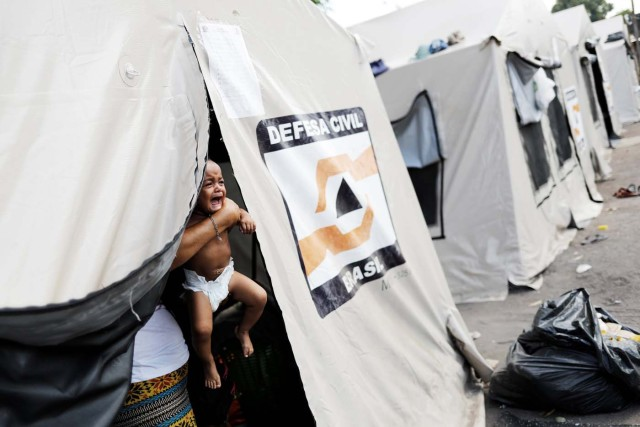 "A Venezuelan woman holds her baby inside a tent outside a gym which has turned into a shelter for Venezuelans and is run by Civil Defense with meals provided by Evangelical churches in Caimbe neighbourhood in Boa Vista, Roraima state, Brazil November 17, 2017. REUTERS/Nacho Doce SEARCH ""VENEZUELAN MIGRANTS"" FOR THIS STORY. SEARCH ""WIDER IMAGE"" FOR ALL STORIES."