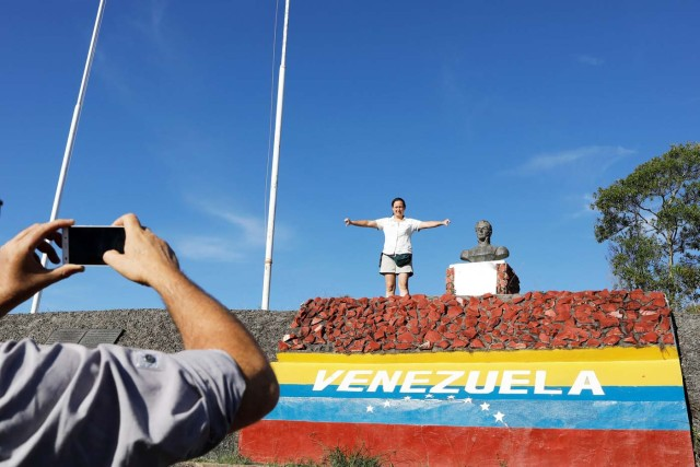 "A Venezuelan man takes a picture of his wife as she gestures after they crossed the border from Venezuela into the Brazilian city of Pacaraima, Roraima state, Brazil November 16, 2017. REUTERS/Nacho Doce SEARCH ""VENEZUELAN MIGRANTS"" FOR THIS STORY. SEARCH ""WIDER IMAGE"" FOR ALL STORIES."