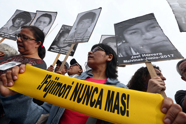 """People holding pictures of victims of the guerrilla conflict in the 80s and 90s march after Peruvian President Pedro Pablo Kuczynski pardoned former President Alberto Fujimori in Lima, Peru, December 25, 2017.  Sign reads: """"Fujimori never again!"""" REUTERS/Mariana Bazo         NO RESALES. NO ARCHIVES."""