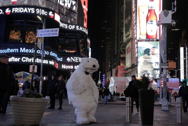 A person dressed in a polar bear costume sits alone on Christmas in Times Square in New York City, New York, U.S., December 25, 2017. Picture taken December 25, 2017. REUTERS/Elizabeth Shafiroff