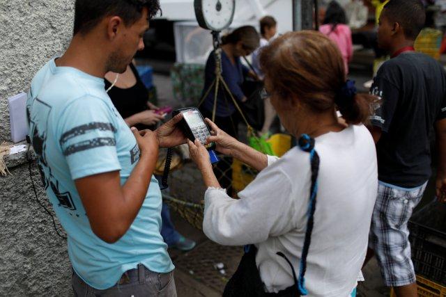 Una mujer usa un dispositivo de punto de venta (POS) en un mercado callejero de verduras en Caracas, Venezuela el 19 de diciembre de 2017. Foto tomada el 19 de diciembre de 2017. REUTERS / Marco Bello