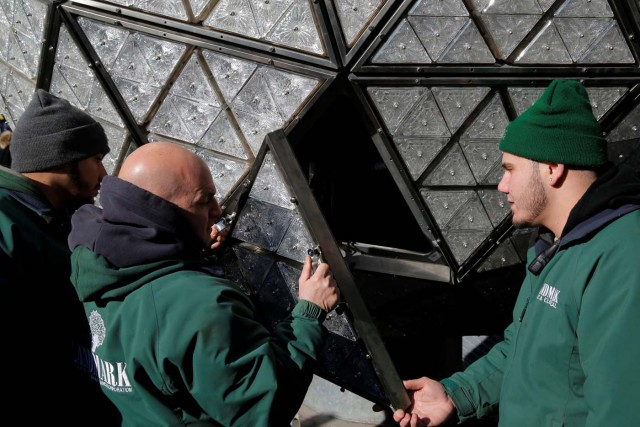 Workers install Waterford Crystal triangles on the Times Square New Year's Eve Ball on the roof of One Times Square in Manhattan, New York, U.S., December 27, 2017. REUTERS/Andrew Kelly