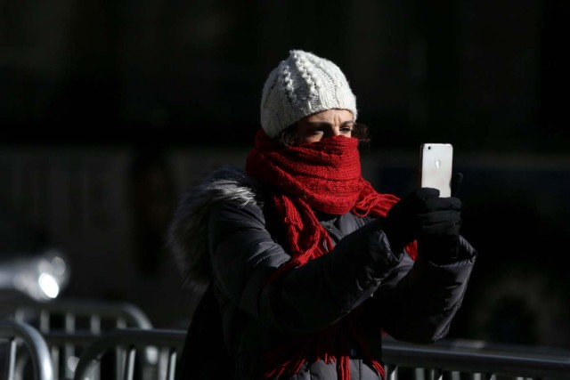 A woman takes a picture as she bundles up against the cold temperature in Times Square in Manhattan, New York, U.S., December 28, 2017. REUTERS/Amr Alfiky