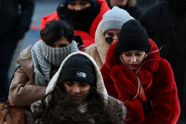 People bundle up against the cold temperature as they walk in Times Square in Manhattan, New York, U.S., December 28, 2017. REUTERS/Amr Alfiky