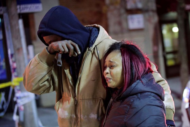 People react near the scene of an apartment fire in Bronx, New York, U.S., December 29, 2017. REUTERS/Eduardo Munoz