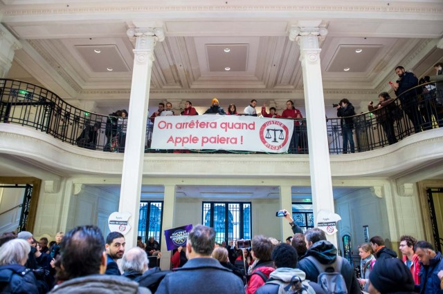 Paris (France), 02/12/2017.- Activists of ATTAC, an anti-globalization organization, hold a banner reading 'We will stop when Apple will pay', in an Apple store to denounce the tax evasion used, according to them, by the American electronics group in Paris, France, 02 December 2017. (Protestas, Francia) EFE/EPA/CHRISTOPHE PETIT TESSON