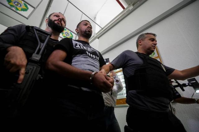"""El narcotraficante brasileño Rogerio Avelino de Souza (c), conocido como """"Rogerio 157"""" y que era el más buscado de Río de Janeiro por ser líder de una banda que protagoniza desde hace meses una """"guerra"""" en la mayor favela de esta ciudad, camina escoltado tras ser arrestado en una operación que contó con apoyo del Ejército hoy, miércoles 6 de diciembre de 2017, en Río de Janeiro (Brasil). EFE/Antonio Lacerda"""