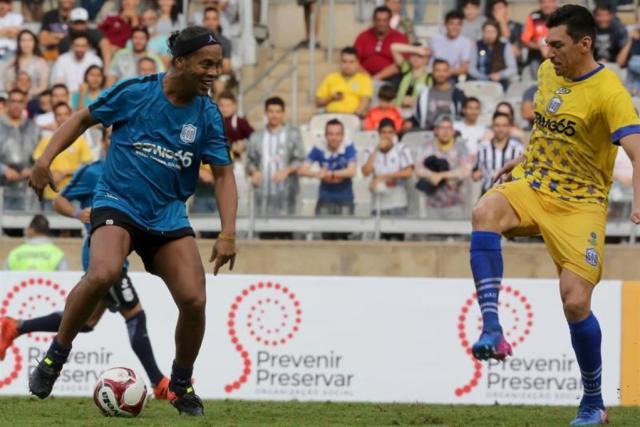 El futbolista brasileño Ronaldinho Gaúcho (i) disputa el balón con Lucio (d) durante un partido benéfico en el estadio Mineirão, en Belo Horizonte (Brasil). EFE