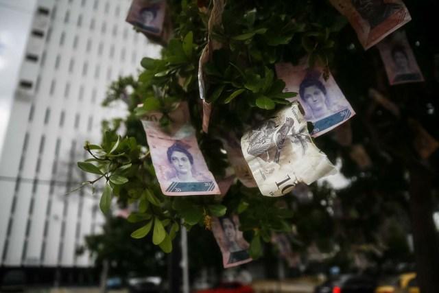 VEN209- MARACAIBO (VENEZUELA) - 27/12/2018 - Detalle de un árbol con billetes venezolanos puestos en sus ramas como protesta por la situación económica hoy, 27 de diciembre del 2017, en Maracaibo (Venezuela). Venezuela ya ha registrado al menos dos crisis por efectivo en los últimos meses, siendo la más grave la que ocurrió a mediados de diciembre pasado después de que el jefe de Estado, Nicolás Maduro, ordenase retirar en tres días el billete de 100 bolívares, para entonces el mayor signo monetario del país. EFE/HUMBERTO MATHEUS