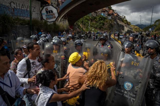 Un grupo de personas protesta frente a miembros de la Policía Nacional Bolivariana (PNB) este jueves 28 de diciembre. EFE/MIGUEL GUTIÉRREZ