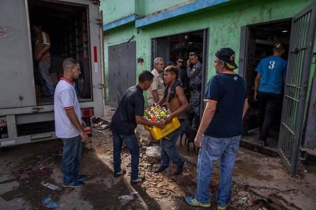 CAR106. CARACAS (VENEZUELA), 28/12/2018.- Un trabajador de una licorera que fue saqueada en horas de la madrugada en el sector La Vega saca productos del local comercial hoy, jueves 28 de diciembre del 2017, en Caracas (Venezuela). Durante la madrugada de este jueves se registraron en varios puntos de Venezuela protestas por la escasez de alimentos para completar el menú navideño, gas y agua, informaron hoy medios locales. EFE/MIGUEL GUTIÉRREZ