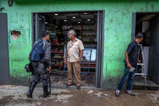 CAR100. CARACAS (VENEZUELA), 28/12/2018.- Un policía ingresa a una licorera que fue saqueada en horas de la madrugada en el sector La Vega hoy, jueves 28 de diciembre del 2017, en Caracas (Venezuela). Durante la madrugada de este jueves se registraron en varios puntos de Venezuela protestas por la escasez de alimentos para completar el menú navideño, gas y agua, informaron hoy medios locales. EFE/MIGUEL GUTIÉRREZ
