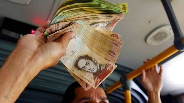 El venezolano Jorge Gutiérrez sostiene un fajo de billetes venezolanos sin apenas valor que quiere cambiar por dinero colombiano, en un autobús de Bogotá, Colombia, el martes 12 de diciembre de 2017. Fernando Vergara AP Foto