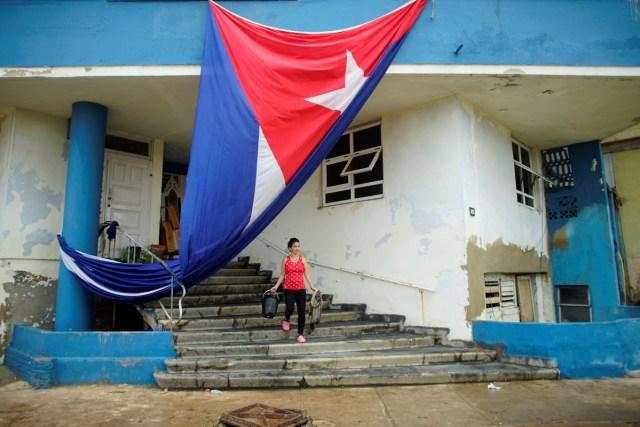 Una mujer limpia la entrada de un edificio junto a una bandera cubana que se colgó a secar después de que el huracán Irma causó inundaciones y un apagón, en La Habana, Cuba, el 11 de septiembre de 2017. REUTERS / Alexandre Meneghini