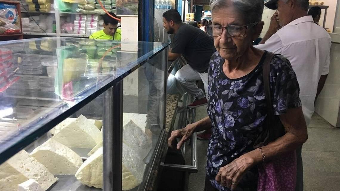 Maritza Díaz, una ama de casa de 72 años, está triste sobre los precios de los productos que se exhiben en la vidriera de un local del mercado de La Limpia en Maracaibo, en el occidente de Venezuela. Gustavo Ocando Alex Especial para el Nuevo Herald