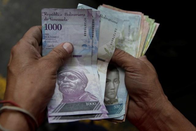 Un trabajador de una gasolinera de PDVSA cuenta bolívares en Caracas. 1 de diciembre de 2017. REUTERS/Marco Bello