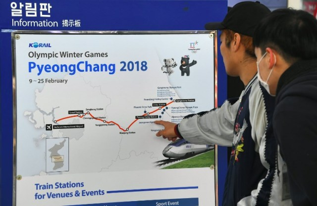 Travellers look at a billboard showing information of a new high-speed train line for the 2018 PyeongChang Winter Olympic Games, at Seoul station in Seoul on December 22, 2017. The railway, part of South Korea's KTX network, cuts travel times significantly, reaching Jinbu - the station for the snow sports in Pyeongchang - in one hour and 20 minutes from Seoul, and another 16 minutes to Gangneung on the east coast, where ice events will take place. / AFP PHOTO / JUNG Yeon-Je