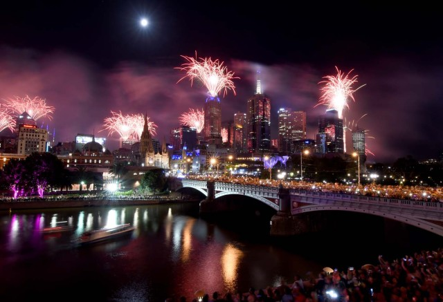 Fireworks light up the sky from building rooftops along the Yarra River during New Year's Eve celebrations in Melbourne early on January 1, 2018. / AFP PHOTO / Mal Fairclough