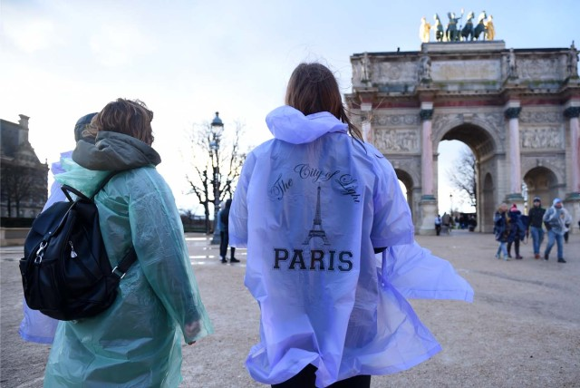 Tourists wearing raincoats stand by the Arc de Triomphe du Carrousel monument by the Louvre Museum on January 1, 2018 in Paris. / AFP PHOTO / GUILLAUME SOUVANT