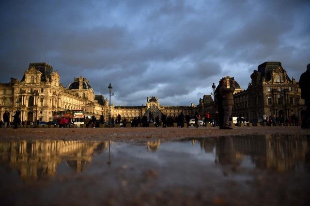 Tourists enjoy the scenery of the Louvre Museum and its pyramid under an overcast sky on January 1, 2018 in Paris. / AFP PHOTO / GUILLAUME SOUVANT