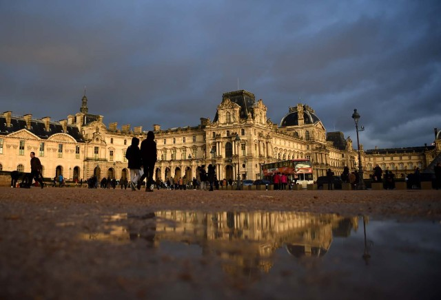 Tourists walk past the Richelieu wing of the Louvre Museum under an overcast sky on January 1, 2018 in Paris. / AFP PHOTO / GUILLAUME SOUVANT