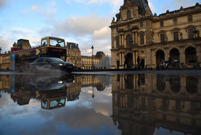A car overtakes a double decker sightseeing bus past the Louvre Museum, reflected in a pool of rain water on January 1, 2018 in Paris. / AFP PHOTO / GUILLAUME SOUVANT