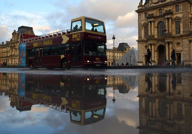 A double decker sightseeing bus drives past the Louvre Museum, reflected in a pool of rain water on January 1, 2018 in Paris. / AFP PHOTO / GUILLAUME SOUVANT