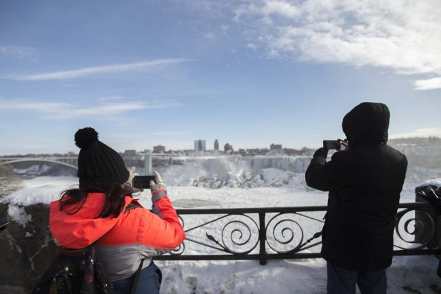 Tourists take photos of the nearly frozen American side of Niagara Falls from Niagara Falls, Ontario on January 3, 2018. The cold snap which has gripped much of Canada and the United States has nearly frozen over the American side of the falls. / AFP PHOTO / Geoff Robins