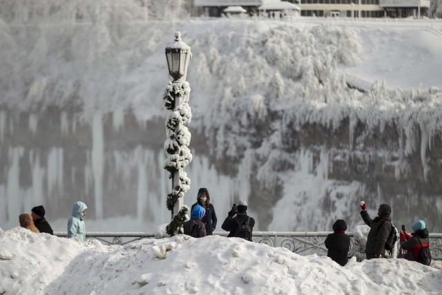 Tourists take photos of the Horseshoe Falls in Niagara Falls, Ontario on January 3, 2018. The cold snap which has gripped much of Canada and the United States has nearly frozen over the American side of the falls. / AFP PHOTO / Geoff Robins