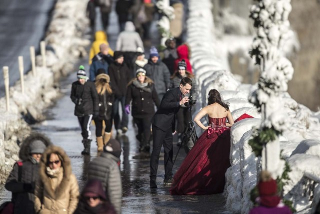 Jonathan Czitkovics and his wife Yvonne Chen take wedding photos in Niagara Falls, Ontario on January 3, 2018. The couple were married this summer in Thailand where they live but wanted to do some wedding photos in Canada, since Jonathan is from Montreal. The cold snap which has gripped much of Canada and the United States has nearly frozen over the American side of the falls. / AFP PHOTO / Geoff Robins