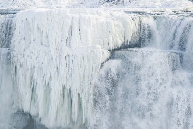 Ice hangs from the top of the American side of Niagara Falls on January 3, 2018. The cold snap which has gripped much of Canada and the United States has nearly frozen over the American side of the falls. / AFP PHOTO / Geoff Robins