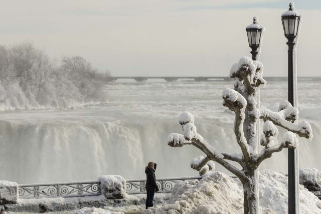 Tourists look out past the frozen railings at the Horseshoe Falls in Niagara Falls, Ontario on January 3, 2018. The cold snap which has gripped much of Canada and the United States has nearly frozen over the American side of the falls. / AFP PHOTO / Geoff Robins
