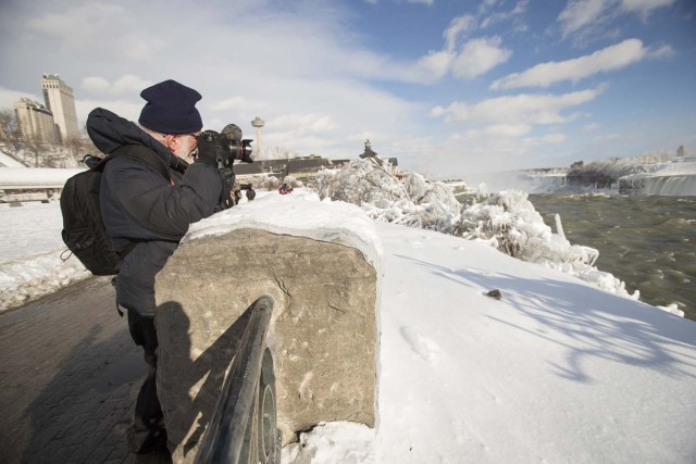A tourist takes photos of the Horseshoe Falls in Niagara Falls, Ontario on January 3, 2018. The cold snap which has gripped much of Canada and the United States has nearly frozen over the American side of the falls. / AFP PHOTO / Geoff Robins