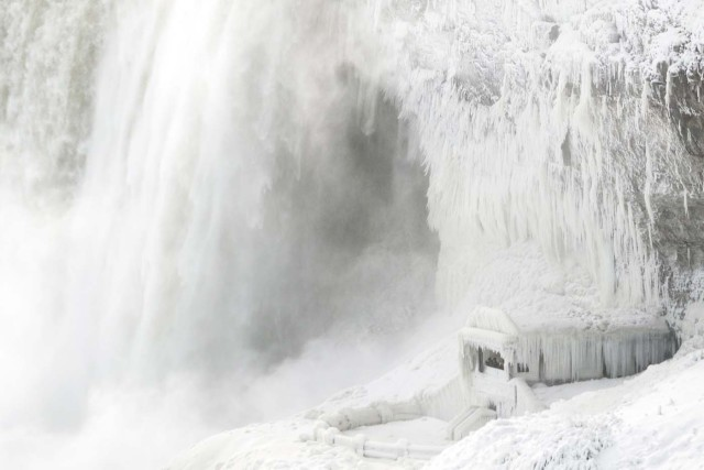 Ice coats the rocks and observation deck at the base of the Horseshoe falls in Niagara Falls, Ontario on January 3, 2018. The cold snap which has gripped much of Canada and the United States has nearly frozen over the American side of the falls. / AFP PHOTO / Geoff Robins