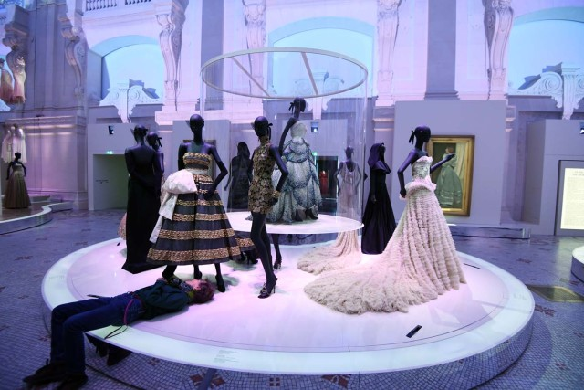 (FILES) This file picture taken on July 3, 2017 shows a man adjusting a dress prior to the opening of the Dior exhibition that celebrates the seventieth anniversary of the Christian Dior fashion house, at the Museum of Decorative Arts (Musee des Arts Decoratifs) in Paris. 708 000 people visited the exhibition dedicated to Christian Dior from July 5, 2017 to January 7, 2018 in Paris. / AFP PHOTO / ALAIN JOCARD