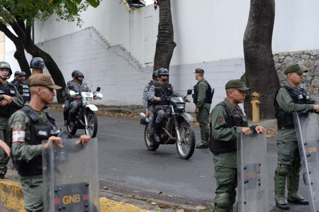 """Security forces block access to the morgue in Caracas where the bodies of rogue pilot Oscar Perez and six other """"terrorists"""" killed during a bloody police assault to arrest them, are being kept on January 17, 2018. Venezuela's government announced Tuesday that Perez was among seven """"terrorists"""" killed when police swooped on them outside Caracas on Monday, setting off a fierce gunbattle in which two police officers were also killed. Perez had been wanted since he used a stolen helicopter to bomb Venezuela's Supreme Court at the height of anti-government protests last June. / AFP PHOTO / Federico PARRA"""