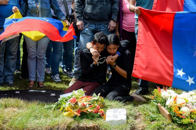Relatives of Jose Diaz Pimentel, one of the six other dissidents gunned down along with former elite police officer Oscar Perez in a bloody police operation, cry next to his grave as he and rebel Abraham Agostini are buried at a cemetery in Caracas on January 20, 2018. Perez, Venezuela's most wanted man since he flew a stolen police helicopter over Caracas dropping grenades on the Supreme Court and opening fire on the Interior Ministry, had gone on social media while the operation was under way on January 16 to say he and his group wanted to surrender but were under unrelenting sniper fire. That has raised questions about the government's account that the seven were killed after opening fire on police who had come to arrest them. / AFP PHOTO / Federico PARRA