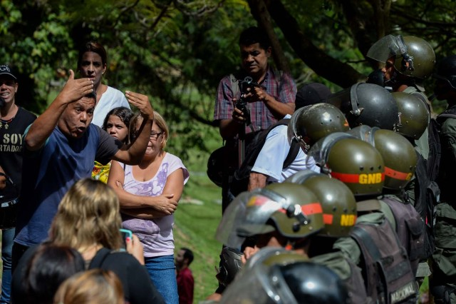 An activist opposing Venezuelan President Nicolas Maduro argues with security forces blocking their access to the funeral of Jose Diaz Pimentel and Abraham Agostini, two of the six other dissidents gunned down along with former elite police officer Oscar Perez in a bloody police operation, at a cemetery in Caracas on January 20, 2018. Perez, Venezuela's most wanted man since June when he flew a stolen police helicopter over Caracas dropping grenades on the Supreme Court and opening fire on the Interior Ministry, had gone on social media while the operation was under way on January 16 to say he and his group wanted to surrender but were under unrelenting sniper fire. That has raised questions about the government's account that the seven were killed after opening fire on police who had come to arrest them. / AFP PHOTO / Federico PARRA