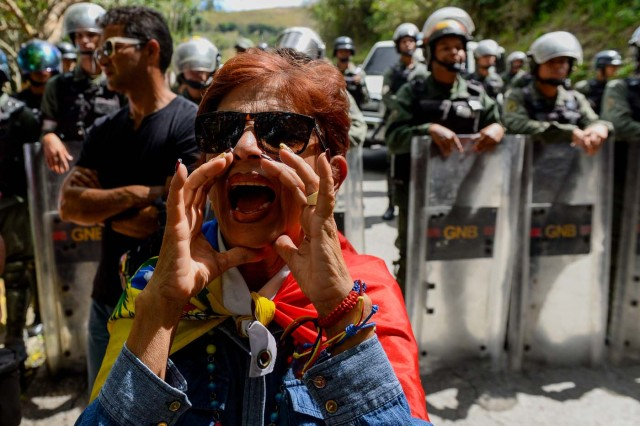 An activist opposing Venezuelan President Nicolas Maduro shouts slogans as security forces block their access to the funeral of Jose Diaz Pimentel and Abraham Agostini, two of the six other dissidents gunned down along with former elite police officer Oscar Perez in a bloody police operation, at a cemetery in Caracas on January 20, 2018. Perez, Venezuela's most wanted man since June when he flew a stolen police helicopter over Caracas dropping grenades on the Supreme Court and opening fire on the Interior Ministry, had gone on social media while the operation was under way on January 16 to say he and his group wanted to surrender but were under unrelenting sniper fire. That has raised questions about the government's account that the seven were killed after opening fire on police who had come to arrest them. / AFP PHOTO / Federico PARRA