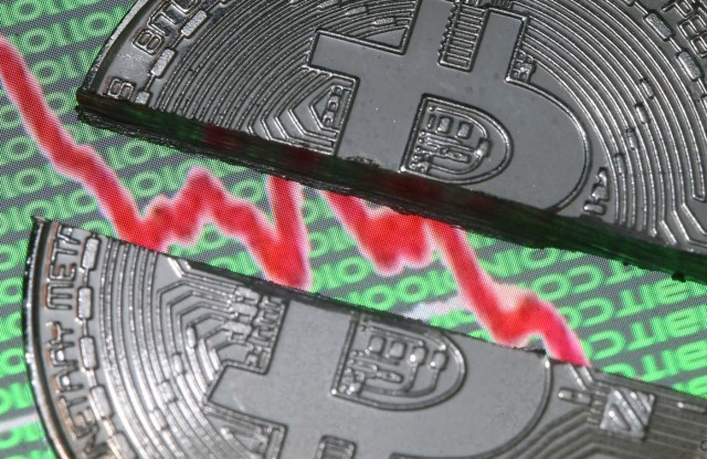 Broken representation of the Bitcoin virtual currency, placed on a monitor that displays stock graph and binary codes, are seen in this illustration picture, December 21, 2017. REUTERS/Dado Ruvic/Illustration