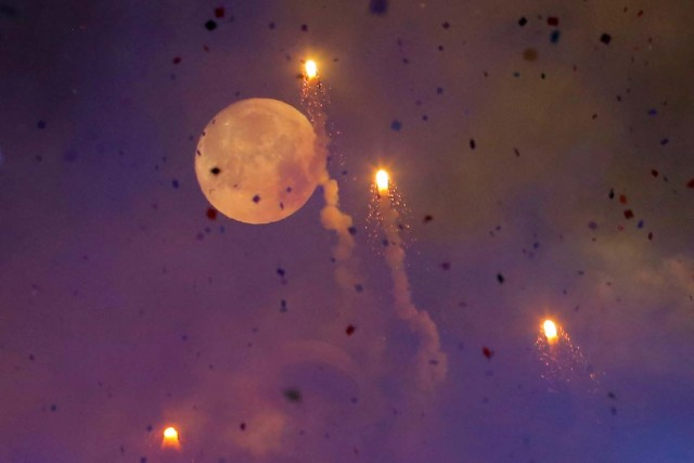 The moon is seen through fireworks over Times Square during New Year's celebrations in Manhattan, New York, U.S., January 1, 2018. REUTERS/Andrew Kelly