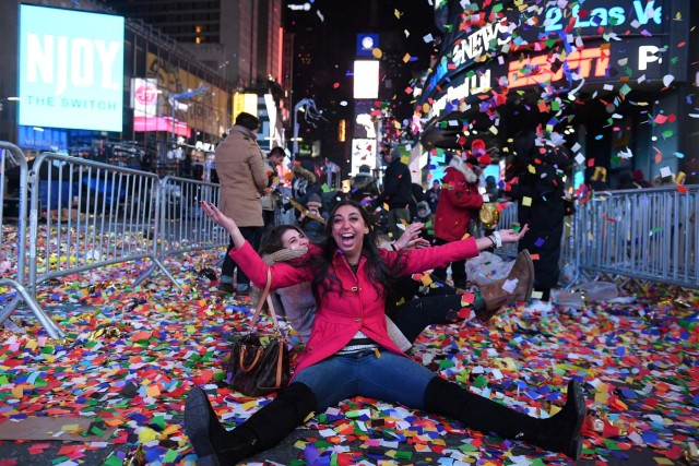 Revelers play in confetti in Times Square during New Year celebrations in Manhattan, New York, U.S., January 1, 2018. REUTERS/Darren Ornitz
